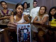 Patricia Villanueva tient une photo de son frère, Freddy, entourée par les membres de la famille.