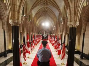 Un gardien de sécurité monte la garde devant le hall d'honneur au Parlement canadien.