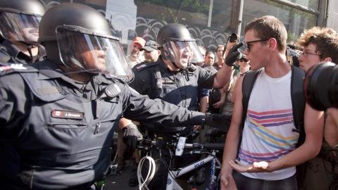 Des manifestants font face à des policiers antiémeutes près du périmètre de sécurité du G20 à Toronto, le 26 juin 2010.