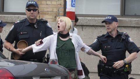 Une femme est arrêtée devant le centre de détention provisoire aménagé dans un studio de cinéma à Toronto, le 27 juin 2010.