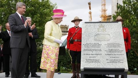 Le premier ministre  Harper et la reine regardent la pierre  angulaire du Musée canadien des droits de la personne, après son  dévoilement, le 3 juillet 2010.