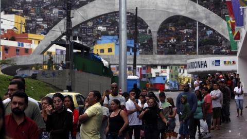 Des Brésiliens font la queue devant un bureau de vote de la favela Rocinha, à Rio de Janeiro.