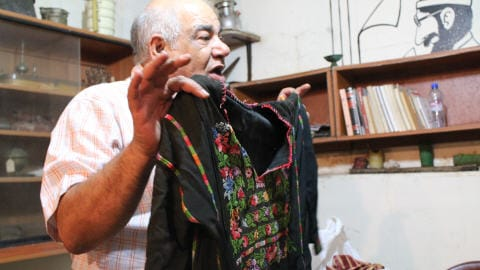 Mohamed Khatib montre une vieille robe traditionnelle palestinienne.