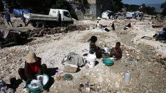 Installées dans les débris, des femmes nettoient leurs vêtements près de Port-au-Prince.