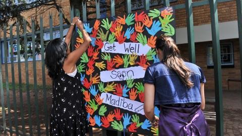 Des enfants posent un message de solidarité pour Nelson Mandela sur une clôture de leur école.