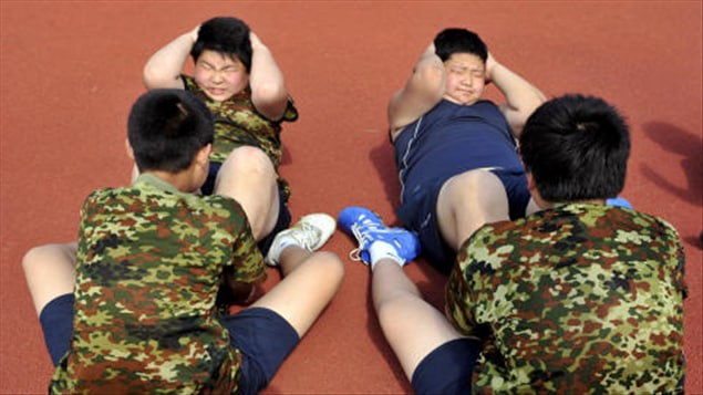 Des enfants obèses chinois peinent à faire des redressements assis. (archives)