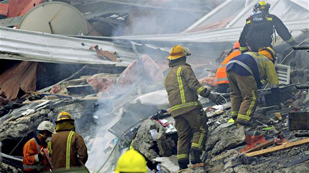 Les pompiers fouillent dans les débris des immeubles détruits.