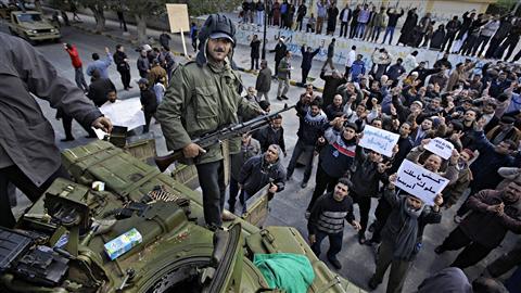 Un homme armé se tenait debout, dimanche, sur un tank saisi à l'armée libyenne.
