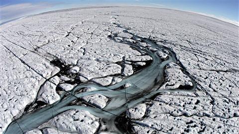 Rivière de fonte sur la calotte polaire du Groenland. En 2017, des chercheurs ont confirmé que les deux plus grandes sources mondiales de la montée du niveau de la mer sont maintenant le Groenland et nos propres glaciers, notamment ceux qui ceinturent toute la côte arctique canadienne. Photo Credit: NASA https://www.rcinet.ca/fr/2017/11/09/groenland-glaciers-canadiens-ocean-arctique-augmentation-niveau-mers-oceans/