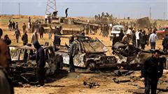 Des Libyens observent les dégâts causés par les frappes aériennes contre l'armée libyenne à environ 35 kilomètres au sud-ouest de Benghazi.