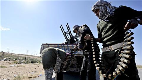 Des rebelles préparent une mitrailleuse antiaérienne aux abords de la ville d'Ajdabiya.
