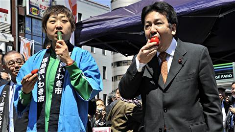 Le secrétaire en chef du cabinet, Yukio Edano (à droite), et le comédien Shizu-chan croquent à pleines dents dans des légumes en provenance de Fukushima, dans un marché de Tokyo, le 12 avril 2011. Ils veulent ainsi encourager les agriculteurs qui subissent les contrecoups de l'accident nucléaire.