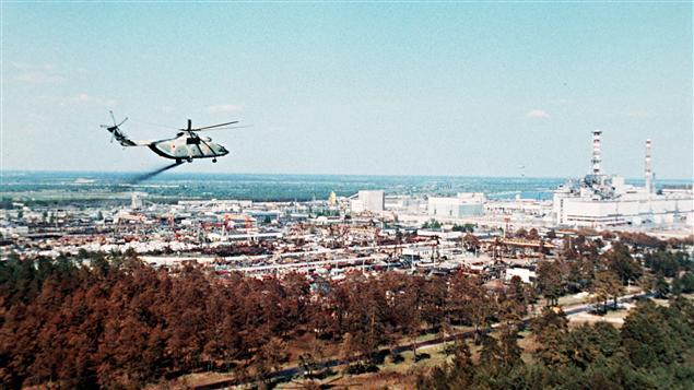 Un hélicoptère militaire répand des produits censés réduire la contamination de l'air quelques jours après l'explosion du réacteur no 4 à la centrale nucléaire de Tchernobyl.
