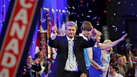 Le premier ministre Stephen Harper, son épouse Laureen, son garçon Ben et sa fille Rachel, saluent des partisans à la suite de l'annonce de la victoire conservatrice, le 2 mai 2011, à Calgary.