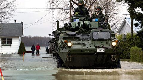 Un véhicule de l'armée dans une rue inondée