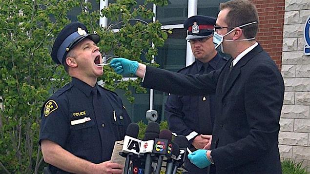 Des policiers d'Orangeville dans la province de l'Ontario montrent la méthode de prélèvement d'un échantillon d'ADN.