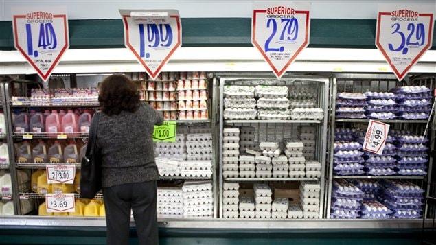 Consommatrice comparant les prix dans un supermarché.