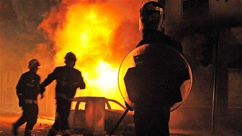 Un policier se tient devant un véhicule en flammes à Croydon, au sud de Londres, le 8 août.