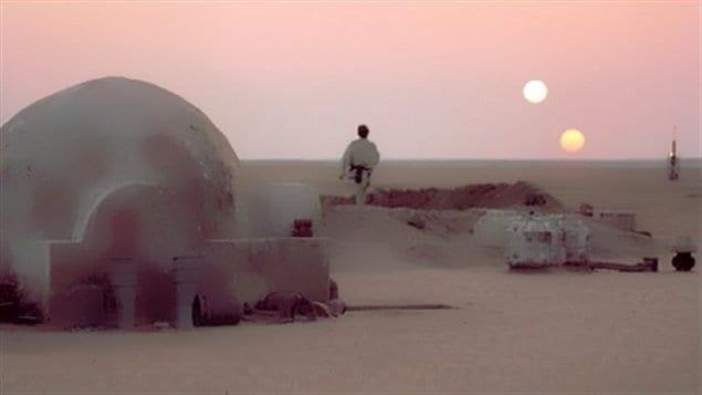 Luke Skywalker assiste à un coucher de soleils sur la planète Tatooine.