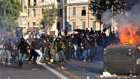 On aperçoit des manifestants, dont certains Black Blocks, ainsi que des flames