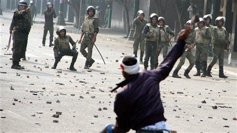 Scène d'affrontements au Caire entre manifestants et forces de l'ordre, dont un membre pointe son arme.