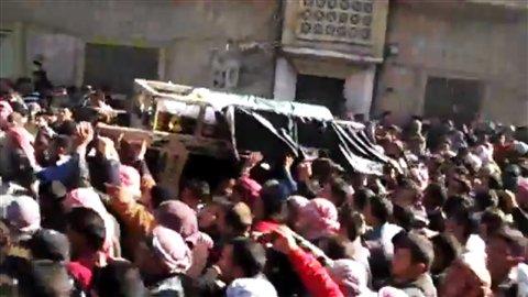 Le cercueil d'un homme tué à Homs circule parmi une foule. L'Associated Press n'est pas en mesure de vérifier l'authenticité de ces images de façon indépendante.