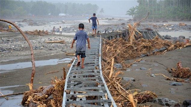 Des enfants jouant sur un pont détruit par les inondations à Iligan, sur l'île de Mindanao, aux Philippines.