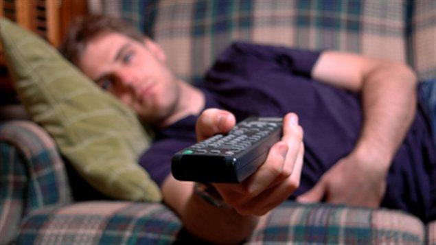 Un homme étendu sur un divan pour regarder la télévision