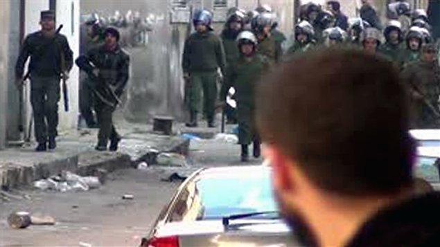 Un manifestant anti-Assad regarde les forces de sécurité du régime qui marchent vers le carré central de la ville d'Homs, le 1er janvier 2012.