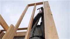 Un ouvrier construit une maison
