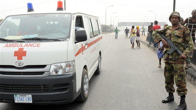 Une ambulance circule près d'un policier nigérian, le 16 janvier.