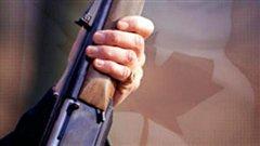 Arme à feu sur fond de feuille d'érable