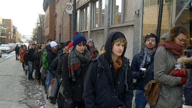 Des étudiants en arts de l'UQAM attendent en file devant Le National sur la rue Ste-Catherine à Montréal pour voter à l'assemblée générale de déclenchement de grève.