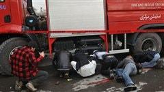 Des journalistes tentent de capter des images derri�re un camion de pompiers au moment o� les forces de s�curit� afghanes tentent de s�curiser le lieu d'une attaque-suicide � Kaboul, en janvier 2011.