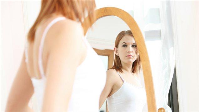 Une adolescente se regarde dans le miroir