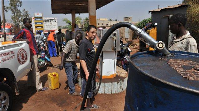 Des Maliens font des réserves d'essence à Bamako.