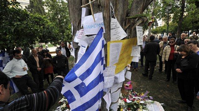 Les gens déposent des offrandes en hommage au retraité de 77 ans qui s'est suicidé devant le Parlement grec