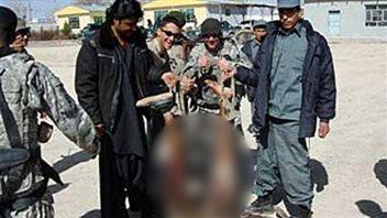 Des soldats américains et des membres des forces afghanes posent avec les restes d'un kamikaze.