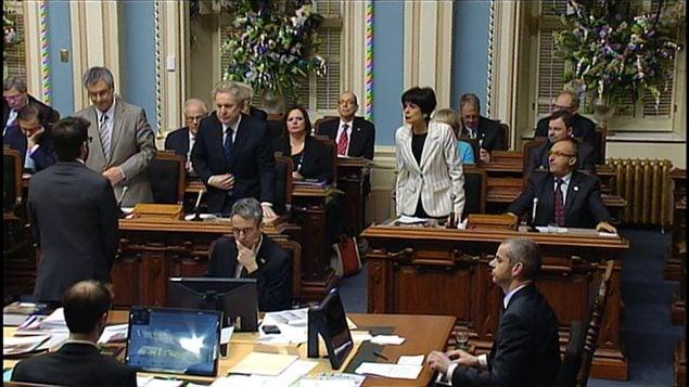 Le premier ministre Jean Charest se lève pour appuyer le principe du projet de loi spéciale déposé par son gouvernement. À gauche, le ministre de la Justice, Jean-Marc Fournier; à droite, la ministre de l'Éducation, Michelle Courchesne.