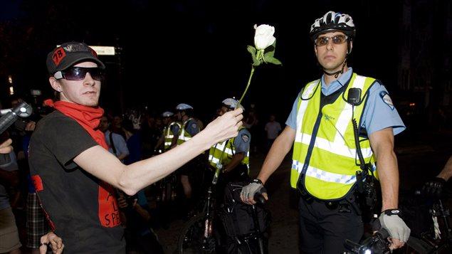 Un manifestant offre une fleur à un policier.