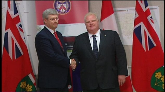 Rob Ford et Stephen Harper se serrent la main.