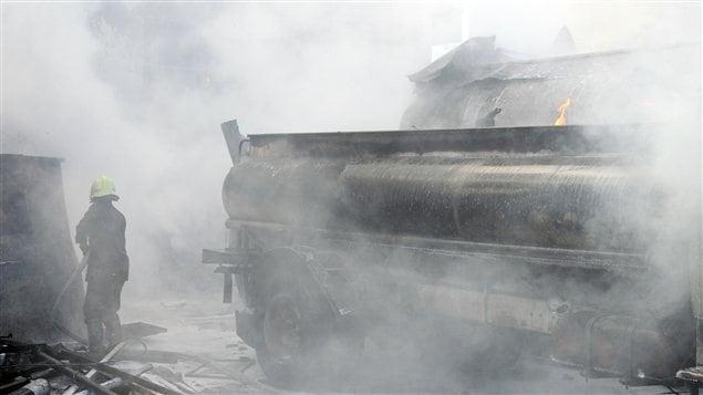Des pompiers tentent de contrôler la situation après l'explosion d'une bombe à Damas, le 15 août 2012.