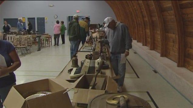 Des curieux observent les objets anciens mis en vente à Zenon Park en Saskatchewan, le 25 août 2012