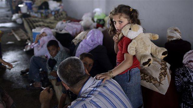 Une fillette syrienne, qui a fui Marea avec sa famille, attend dans un refuge au poste frontalier Bab Al-Salameh.