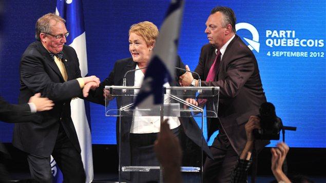 Des gardes du corps de la Sûreté du Québec évacuent Pauline Marois d'urgence au milieu de son discours.