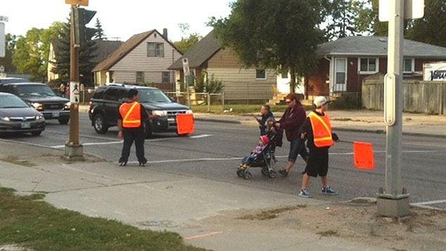 Des patrouilleurs de quartier aident les piétons à traverser la route jeudi près de l'École Archwood à Winnipeg.