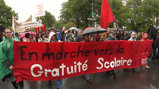 Des manifestants tiennent une banderole en faveur de la gratuité scolaire.