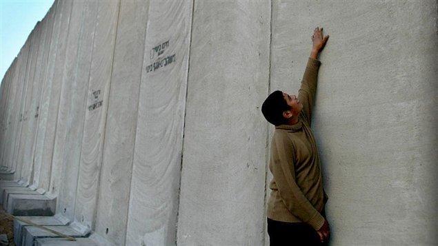 Un jeune Palestinien devant un mur récemment construit dans le village de Nazlat Issa  |© AFP / Yoav Lemmer