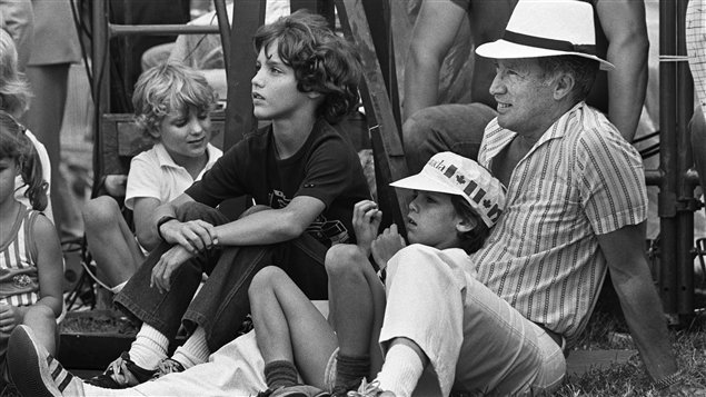 Le premier ministre Pierre-Elliott Trudeau regarde avec ses fils l'ouverture officielle des cérémonies de la fête du Canada sur la colline du Parlement le 1er juillet 1983 à Ottawa.