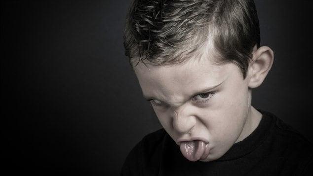 Un garçon tire la langue